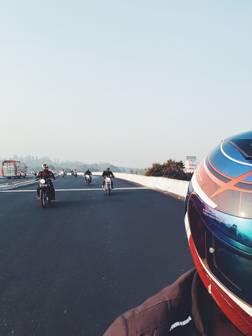 Partial helmet view selfie showing Royal Enfield motorcyclists on the highway