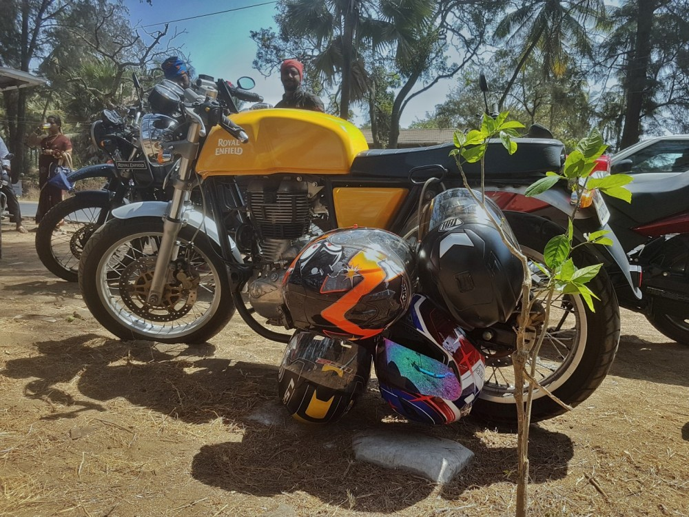 Yellow Royal Enfield Continental GT parked along Dahanu Beach with helmets hanging - THH, MT, LD2 & SMK